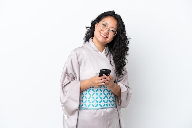 Молодая азиатская женщина в кимоно изолирована на белом фоне, отправляя сообщение с мобильного телефона