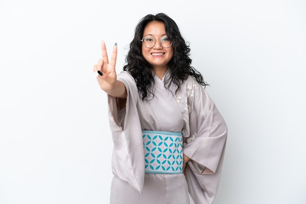 Молодая азиатская женщина в кимоно на белом фоне улыбается и показывает знак победы