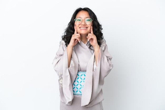 Молодая азиатская женщина в кимоно на белом фоне улыбается со счастливым и приятным выражением лица