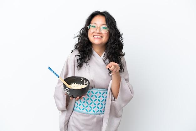 Молодая азиатская женщина в кимоно, изолированном на белом фоне, удивлена и показывает вперед, держа миску лапши с палочками для еды
