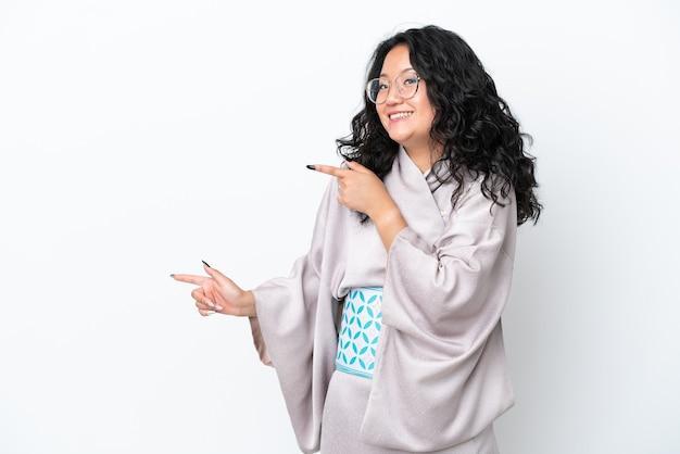 Молодая азиатская женщина в кимоно на белом фоне удивлена и указывает сторону