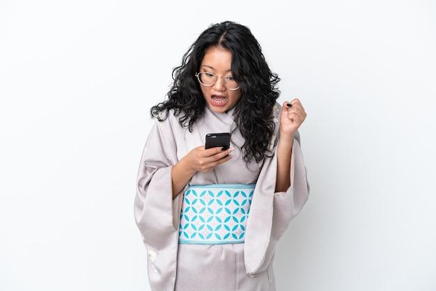 Молодая азиатская женщина в кимоно на белом фоне удивлена и отправляет сообщение