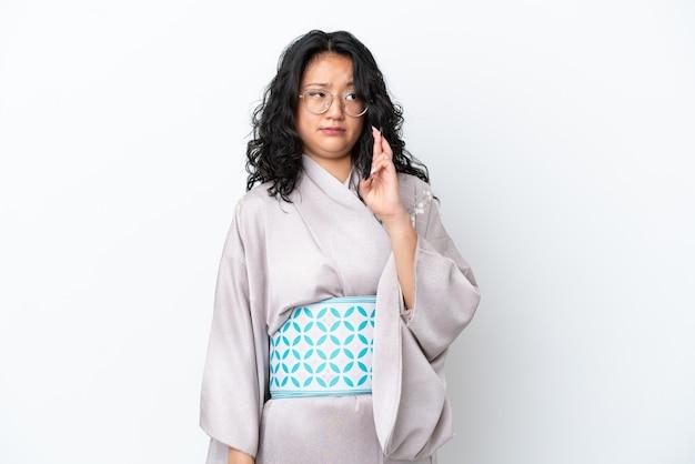 Молодая азиатская женщина в кимоно изолирована на белом фоне со скрещенными пальцами и желает лучшего
