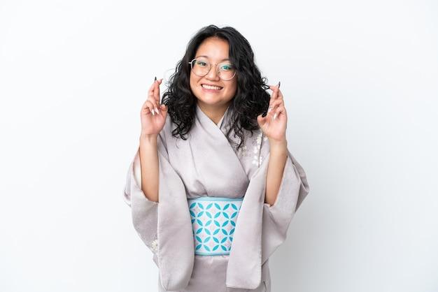 Молодая азиатская женщина в кимоно изолирована на белом фоне со скрещенными пальцами