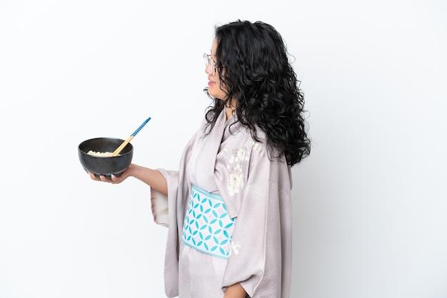 Молодая азиатская женщина в кимоно изолирована на белом фоне со счастливым выражением лица, держа миску лапши с палочками для еды