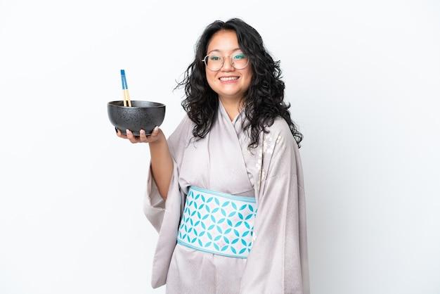 箸で麺のボウルを保持しながら幸せな表情で白い背景で隔離の着物を着て若いアジアの女性