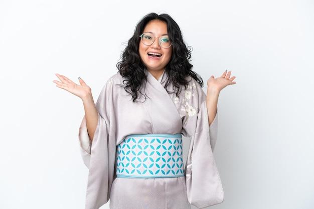 Молодая азиатская женщина в кимоно изолирована на белом фоне с шокированным выражением лица