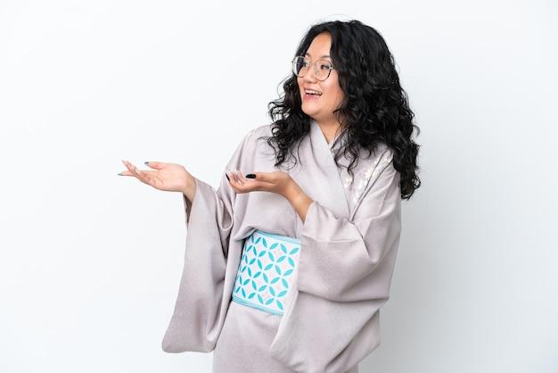 Молодая азиатская женщина в кимоно изолирована на белом фоне с удивленным выражением лица