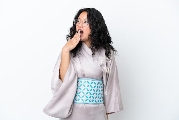 あくびをし、手で大きく開いた口を覆う白い背景で隔離の着物を着ている若いアジアの女性