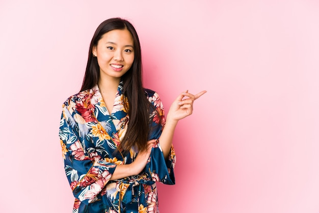Young asian woman wearing a kimono pajama smiling cheerfully pointing with forefinger away