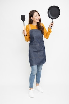 Young asian woman wearing kitchen apron cooking and holding pan isolated on white background