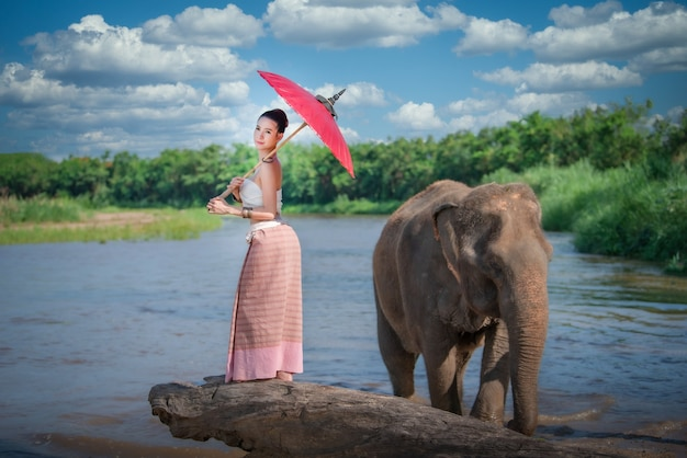 Молодая азиатская женщина в костюме традиционного стиля ланна со слоном в чиангмае, таиланд.
