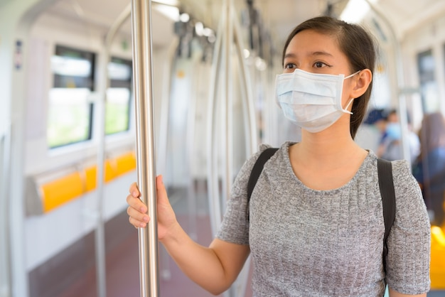 コロナウイルスの発生から保護するためにマスクを着用し、電車の中で距離を置いて立っている若いアジアの女性