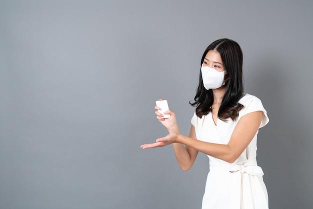 마스크를 착용하고 회색 벽에 코로나 바이러스 (코로나 19)를 보호하기 위해 알코올 스프레이를 사용하는 젊은 아시아 여성