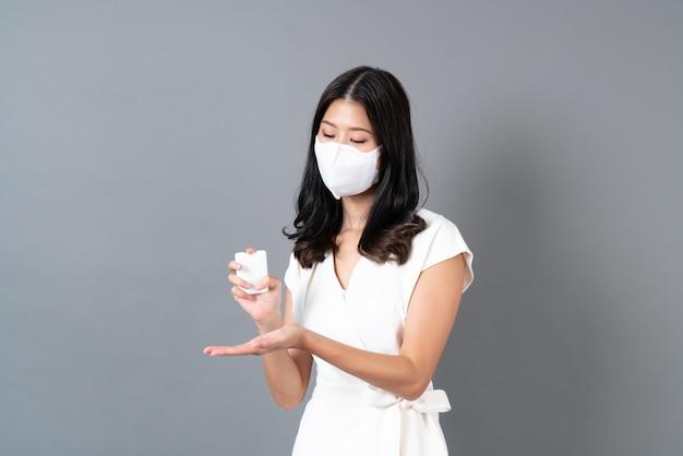 마스크를 착용하고 코로나 바이러스 (covid-19)를 보호하기 위해 알코올 스프레이를 사용하는 젊은 아시아 여성