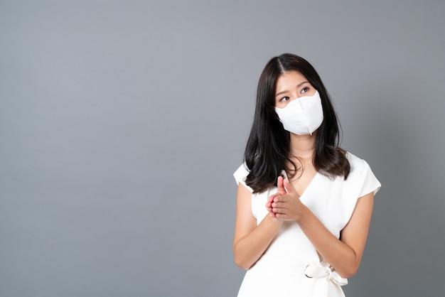 Молодая азиатская женщина в маске для защиты от коронавируса на сером