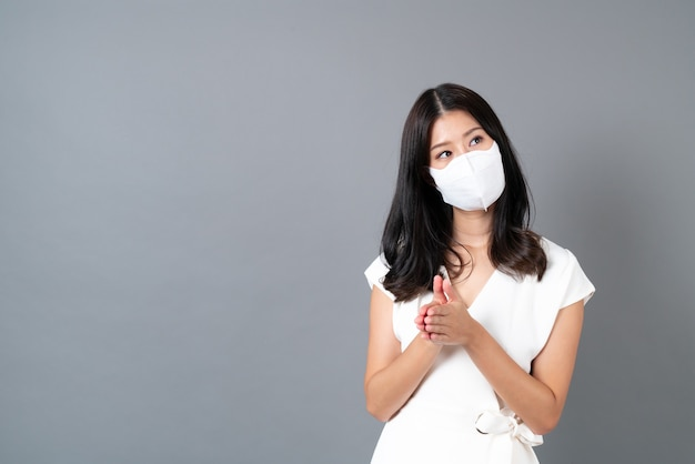 Young asian woman wearing mask for protecting coronavirus on grey
