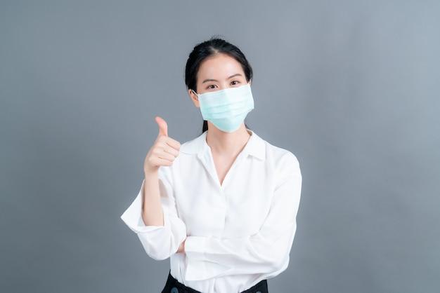 의료용 안면 마스크를 쓴 젊은 아시아 여성이 필터 먼지 pm2.5 오염 방지, 스모그 방지, covid-19를 보호하고 엄지손가락을 치켜듭니다.