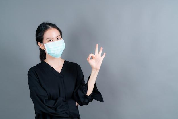 의료용 얼굴 마스크를 착용 한 젊은 아시아 여성이 필터 먼지 pm2.5 오염 방지, 스모그 방지, covid-19 및 ok 사인을 보여줍니다.