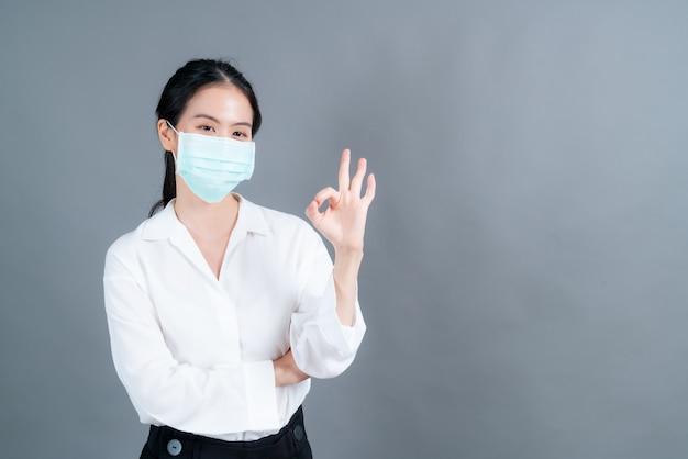 Молодая азиатская женщина в медицинской маске защищает фильтрующую пыль pm2.5 от загрязнения, против смога, covid-19 и показывает знак ок