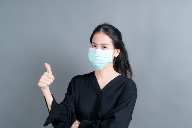 Young asian woman wearing medical face mask protects filter dust pm2.5 anti-pollution, anti-smog, covid-19 and giving thumbs up