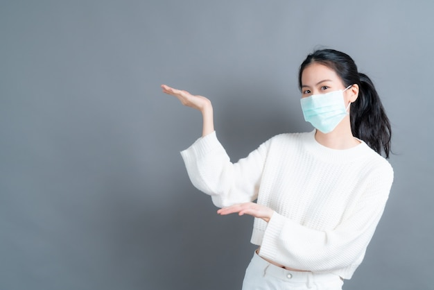 Young asian woman wearing medical face mask protects filter dust pm2.5 anti-pollution, anti-smog, and covid-19 with hand presenting on side