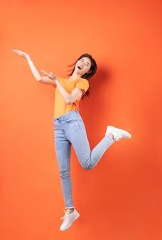 オレンジ色にジャンプするオレンジ色のtシャツを着ている若いアジアの女性