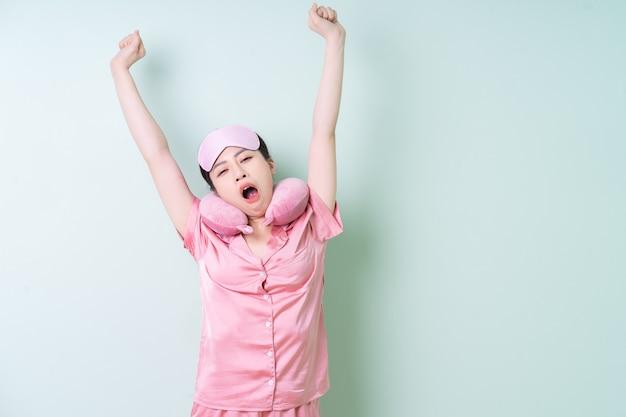 緑の背景にパジャマを着て若いアジアの女性
