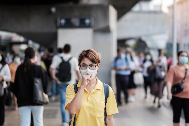 公共の駅で新規コロナウイルス(2019-ncov)または武漢コロナウイルスに対する保護マスクを身に着けている若いアジア女性は、呼吸器感染症を引き起こす伝染性ウイルスです。