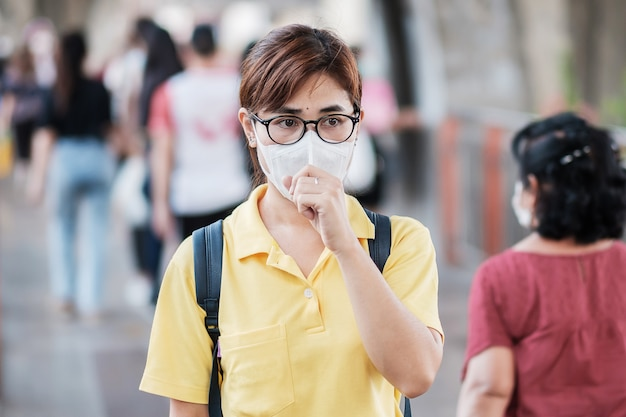 Young asian woman wearing protection mask against novel coronavirus (2019-ncov) or wuhan coronavirus at public train station,is a contagious virus that causes respiratory infection.healthcare concept
