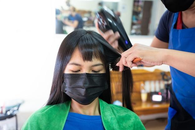 保護マスクを身に着けている若いアジアの女性は、美容院で美容師によってヘアドライヤーで乾いた髪を取得します。クライアントに髪を乾かす美容師。ビューティーサロン、ヘアケアのコンセプト。