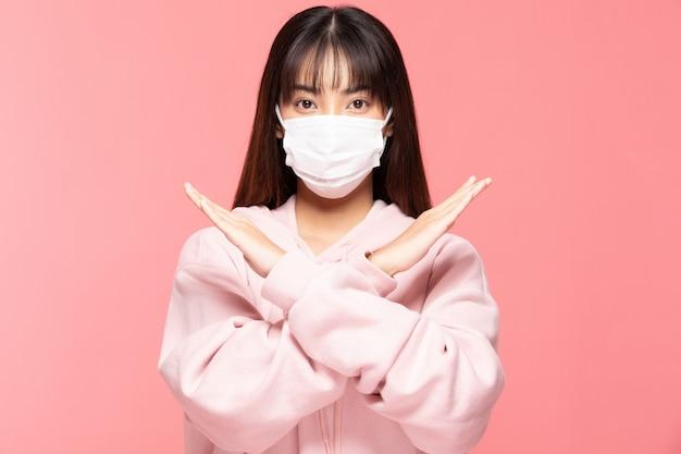 保護されたウイルスやピンク色の壁、ヘルスケア、コロナウイルスのコンセプトにクロスハンドストップウイルスを作る大気汚染のためのサージカルマスクを身に着けている若いアジア女性