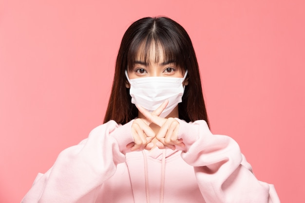 Young asian woman wearing protection mask or surgical mask for protected virus and air pollution making cross hand stop virus on pink wall,health care and coronavirus concept