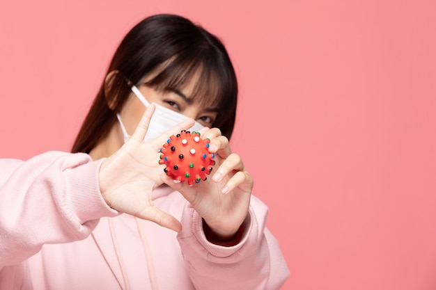 Young asian woman wearing protection mask or surgical mask for protected virus and air pollution making hand stop and hold virus on hand on pink wall,health care and coronavirus concept