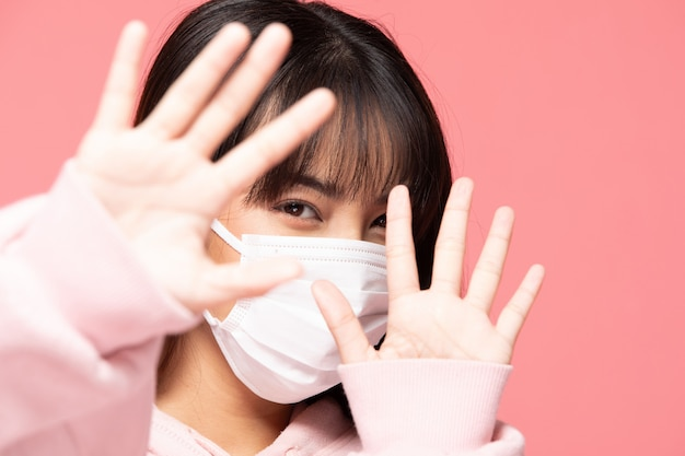 Young asian woman wearing protection mask or surgical mask for protected virus and air pollution making hand stop virus on pink wall,health care and coronavirus concept