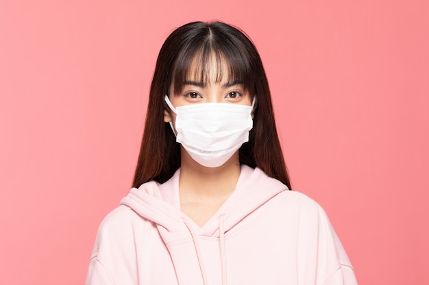 Young asian woman wearing protection mask or surgical mask for protected virus and air pollution on pink wall,health care and coronavirus concept
