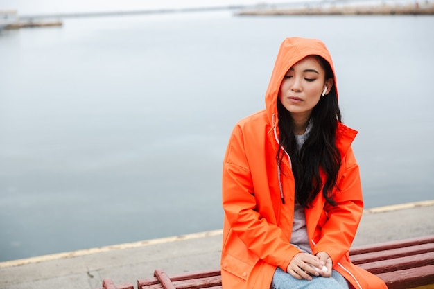 Young asian woman wearing raincoat spending time outdoors walking at the coastland, listening to music with wireless earphones