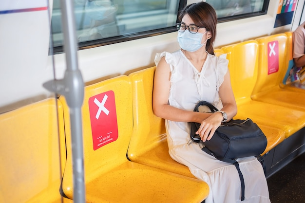 Молодая азиатская женщина нося хирургическую лицевую маску защищает перегиб коронавируса