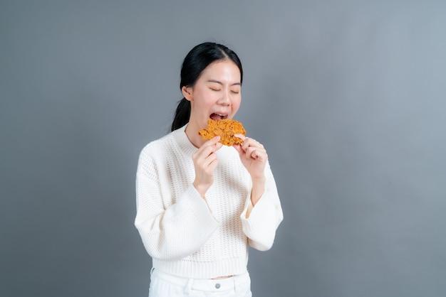 Молодая азиатская женщина носит свитер с счастливым лицом и любит есть жареную курицу на сером фоне