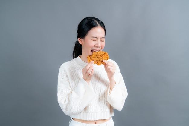 Молодая азиатская женщина в свитере с счастливым лицом любит есть жареную курицу на серой поверхности