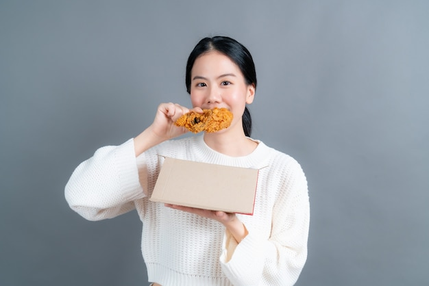 Young asian woman wearing sweater with happy face and enjoy eating fried chicken on grey background