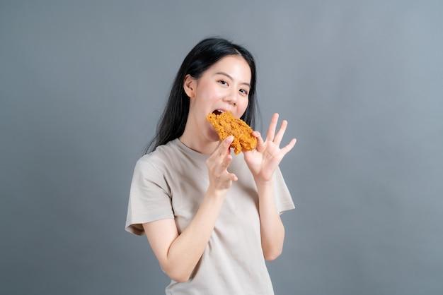 Молодая азиатская женщина в футболке со счастливым лицом и любит есть жареную курицу на сером фоне