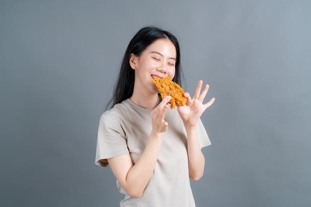행복 한 얼굴로 t- 셔츠를 입고 젊은 아시아 여자 프라이드 치킨을 먹고 즐길 수