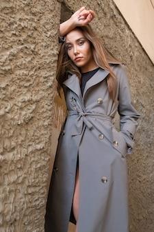 벽 근처에 서 트렌치 코트를 입고 젊은 아시아 여자