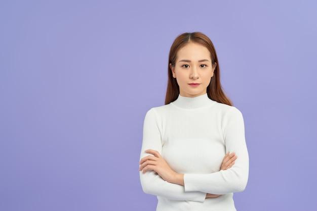 격리 된 흰 벽 행복 한 얼굴에 교차 팔 웃 고 터틀넥 스웨터 서 입고 젊은 아시아 여자. 긍정적 인 사람.