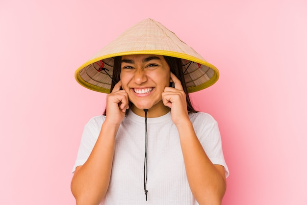 Young asian woman wearing a vietnamese hat isolated young asian woman wearing a vietnamin hatcovering ears with hands.