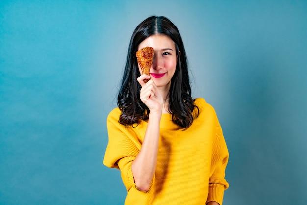 幸せそうな顔と黄色のシャツを着て、青でフライドチキンのバチを食べることを楽しむ若いアジアの女性