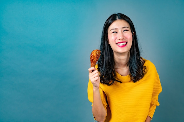 행복 한 얼굴로 노란색 셔츠를 입고 젊은 아시아 여자 프라이드 치킨 드럼 스틱을 먹고 즐길 수