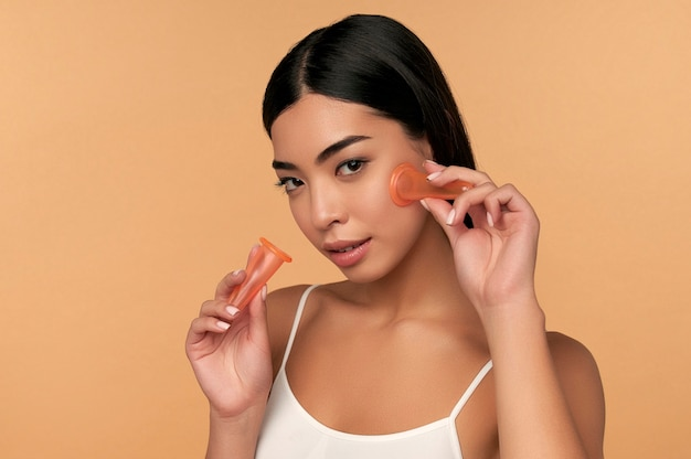 A young asian woman in white lingerie and clean radiant skin makes a vacuum massage of the face with silicone cans on beige