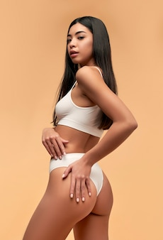 Young asian woman in white lingerie with a toned body and a slender figure on beige. laser hair removal. plastic surgery